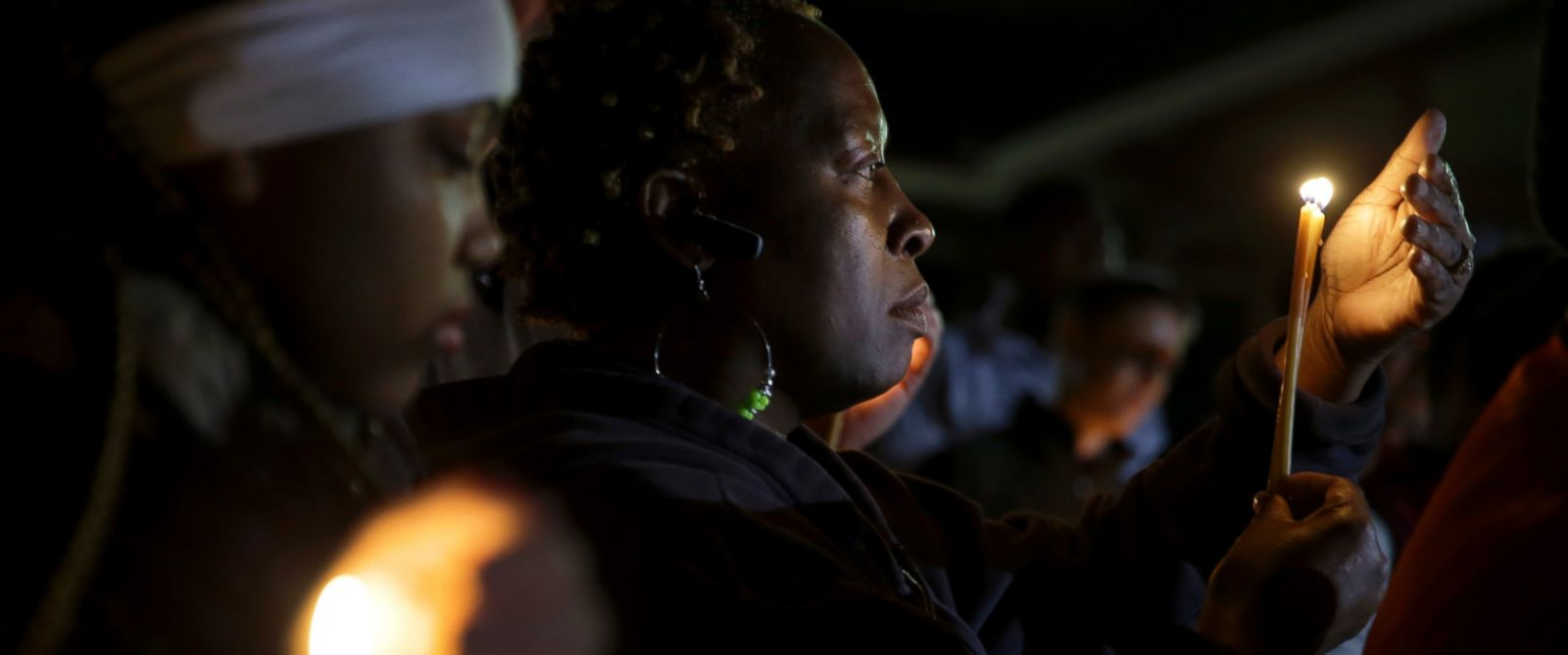 People take part in a candlelight vigil Thursday, March 12, 2015, in Ferguson, Mo. Two police officers were shot early Thursday morning in front of the Ferguson Police Department during a protest following the resignation of the citys police chief.