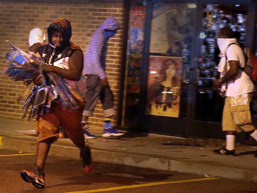 PHOTO: A looter escapes with items from Feel Beauty Supply on West Florissant Avenue in Ferguson early Saturday, Aug. 16, 2014, after protestors clashed with police.