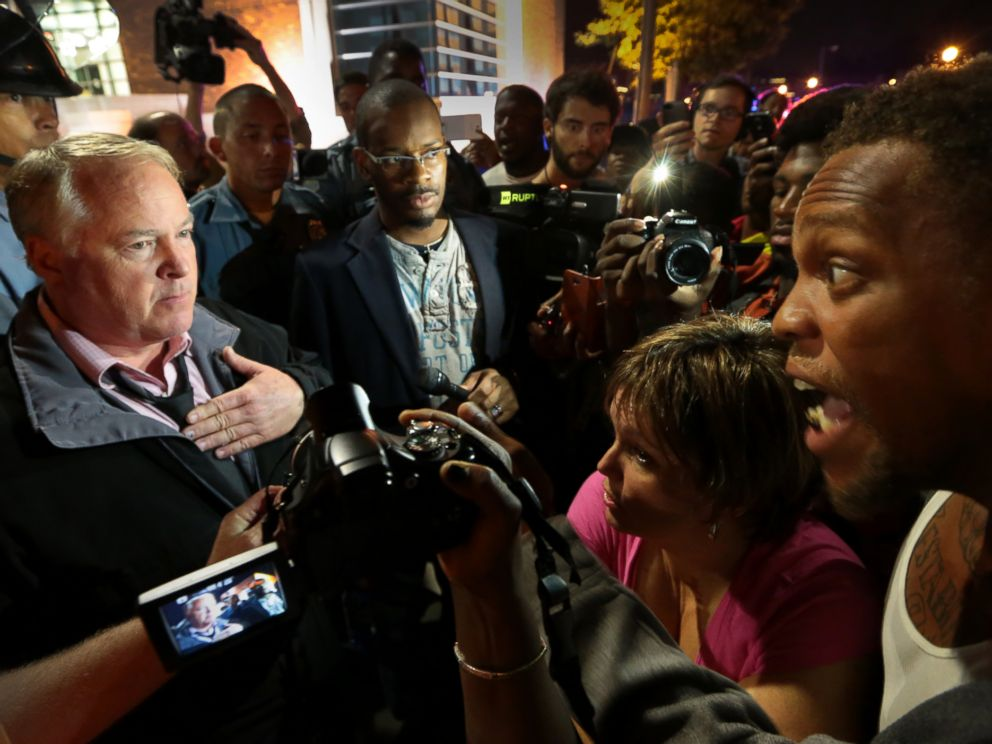 Ferguson Police Chief Tom Jackson, left, speaks before protesters in front of the Ferguson Police Department, on Thursday, Sept. 25, 2014.