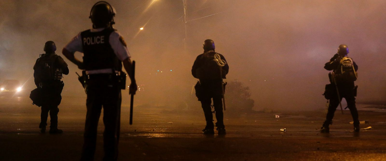 PHOTO: A law enforcement officer watches Sunday, Aug. 17, 2014, as tear gas is fired to disperse a crowd protesting the shooting of teenager Michael Brown last Saturday in Ferguson, Mo.