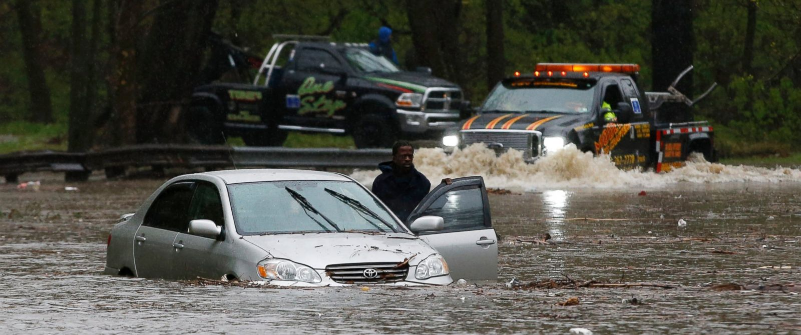 PHOTO: A man waits for a tow truck after getting swamped trying to cross a flooded section of the Cobbs Creek Parkway, April 30, 2014, in Philadelphia.