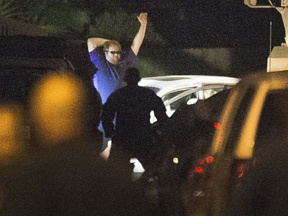 PHOTO: A shooting suspect raises his hands as law enforcement officers surround him following a three-hour standoff, July 9, 2014, in Spring, Texas.