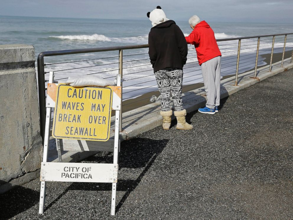 PHOTO: A couple looks at waves breaking near the seawall, Jan. 25, 2016, in Pacifica, Calif. Strong waves caused by El Nino storms ate away part of the sea wall in the coastal community, threatening homes and an apartment building.