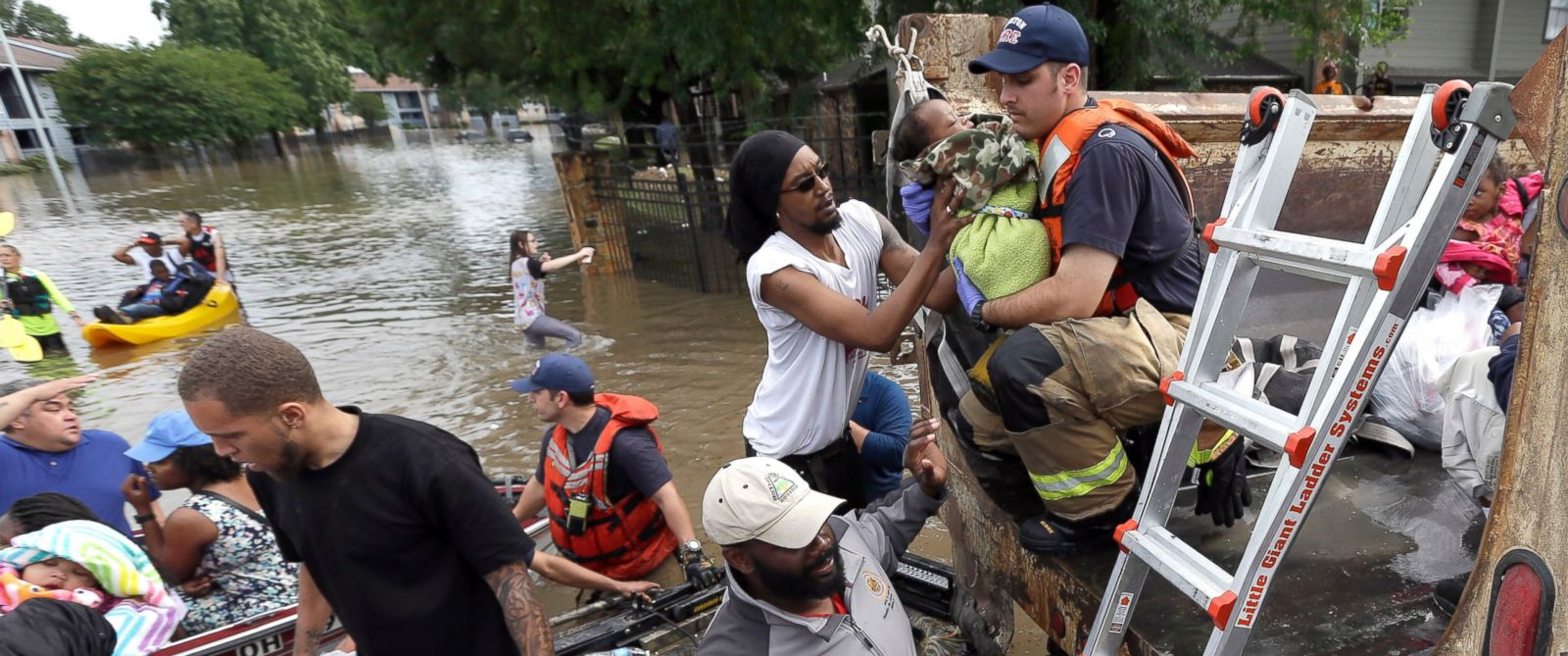 PHOTO: Residents are helped into a dump truck as they evacuate their apartment complex surrounded by floodwaters April 18, 2016, in Houston.