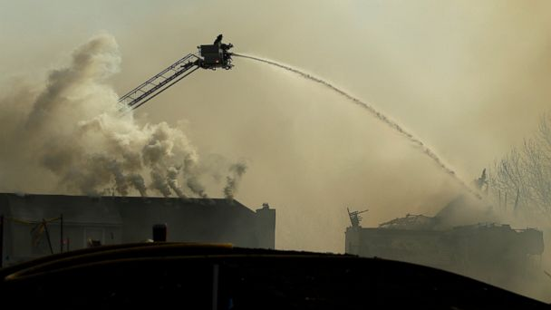 PHOTO: Firefighters fight an eight-alarm fire that began at an apartment complex under construction and than spread to several nearby homes Monday.