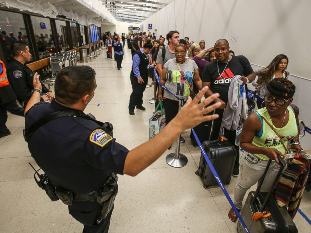 PHOTO: Police officers stand guard as passengers wait in line at Terminal 7 in Los Angeles International Airport, Sunday, Aug. 28, 2016.