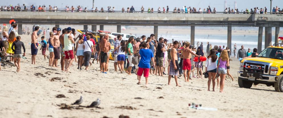 PHOTO: Pedestrians at Venice Beach, Calif. watch as lifeguards bring in a swimmer rescued from the water after a lightning strike, July 27, 2014.
