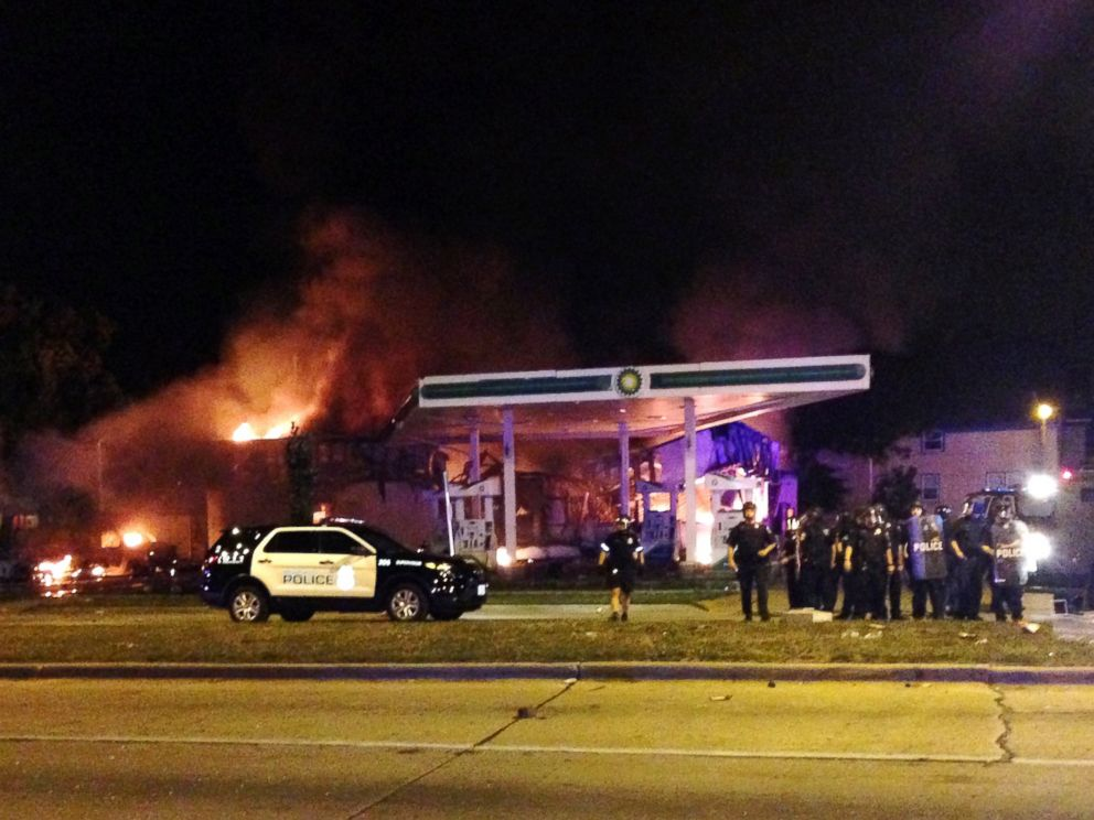 PHOTO: Authorities respond near a burning gas station as dozens of people protest following the fatal shooting of a man in Milwaukee, Saturday, Aug. 13, 2016.