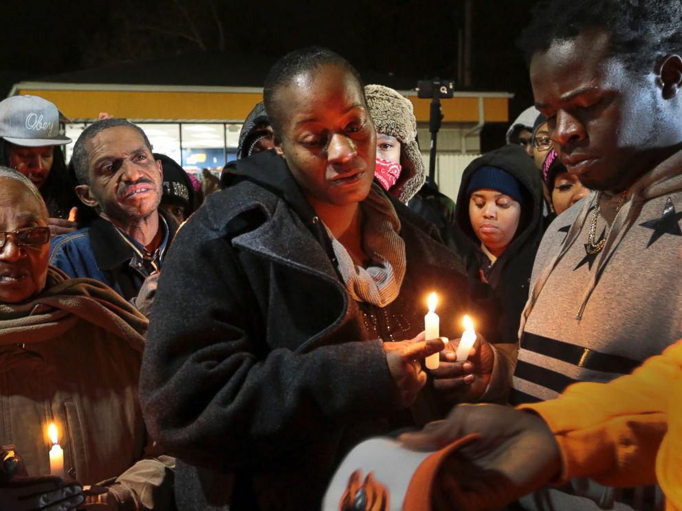 PHOTO: Toni Martin-Green, front center, and her husband Jerome Green, right, participate in a candlelight vigil at a Berkeley, Mo., gas station on Dec. 24, 2014.