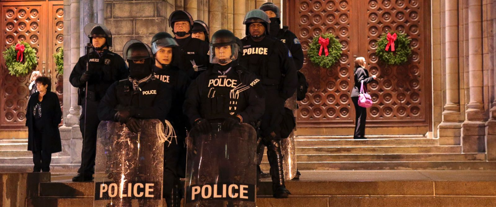 PHOTO: St. Louis Police officers guard the entrance to the Cathedral Basilica before Midnight Mass as protesters held a candlelight vigil, Dec. 24, 2014, in St. Louis.