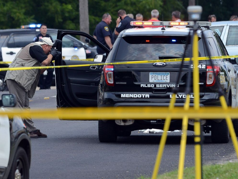 PHOTO: An officer photographs a vehicle driven by a police officer who was shot during a traffic stop in West St. Paul, Minnesota, July 30, 2014.
