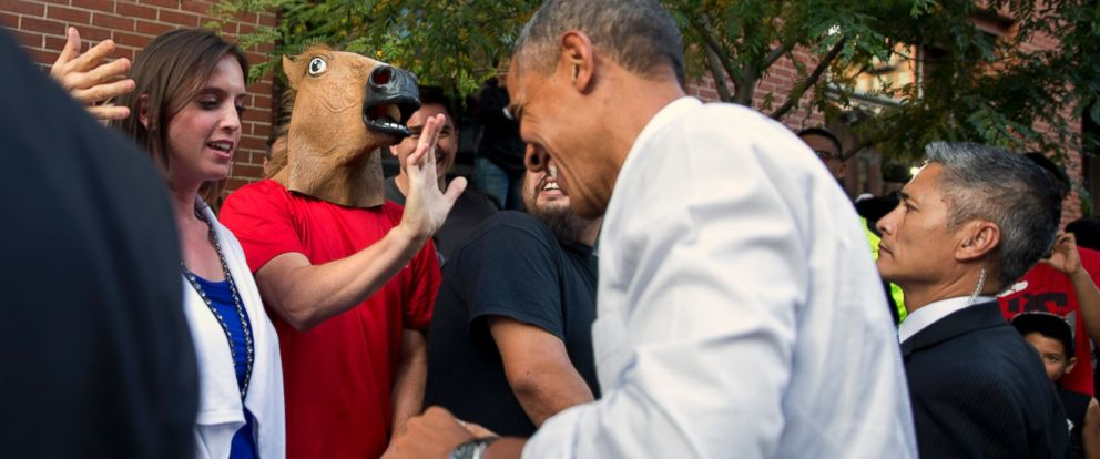 PHOTO: President Barack Obama laughs as he spots a man wearing a horse-head mask during an impromptu walk after having dinner at Wazee Supper Club, July 8, 2014, in Denver.