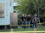 PHOTO: Law enforcement and FBI stand at the back of a boarded-up home where bodies were found earlier in the day Saturday, July 20, 2013 in East Cleveland, Ohio.