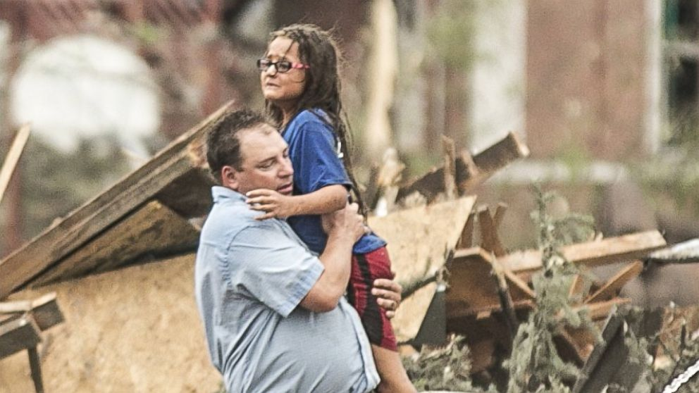 PHOTO: A man holds a girl after she was pulled from the basement of her destroyed home in Pilger, Neb.,June 16, 2014.