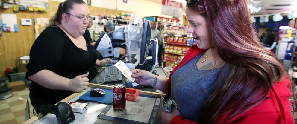 PHOTO: Lauren Fletcher, right, looks at the Powerball lottery ticket she purchased at the Country Store Friday, Jan. 8, 2016, in Odessa, Texas, as the multi-state jackpot reaches $800 million.