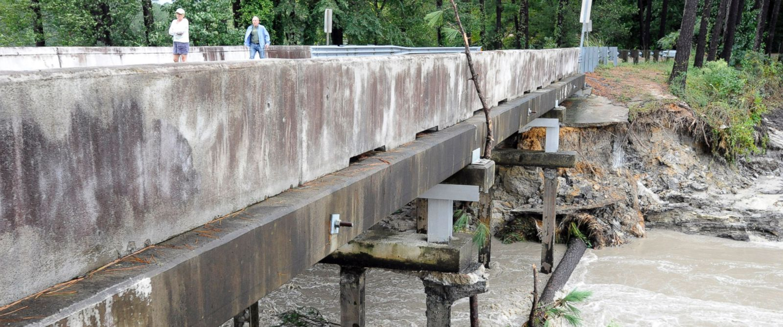 PHOTO: Residents of a lakeside neighborhood walk across Overcreek Bridge by the remains of a failed dam in Columbia, S.C., Oct. 5, 2015.