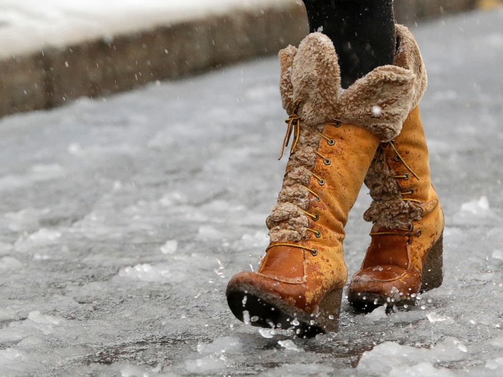 PHOTO: A woman walks over a road covered in slush, Nov. 26, 2014, in Newark, N.J.