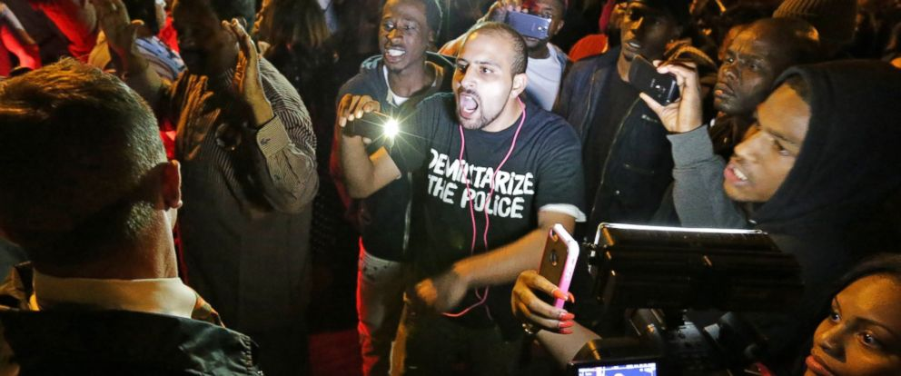 PHOTO: Crowds confront police near the scene in south St. Louis where a man was fatally shot by an off-duty police officer, Oct. 8, 2014.