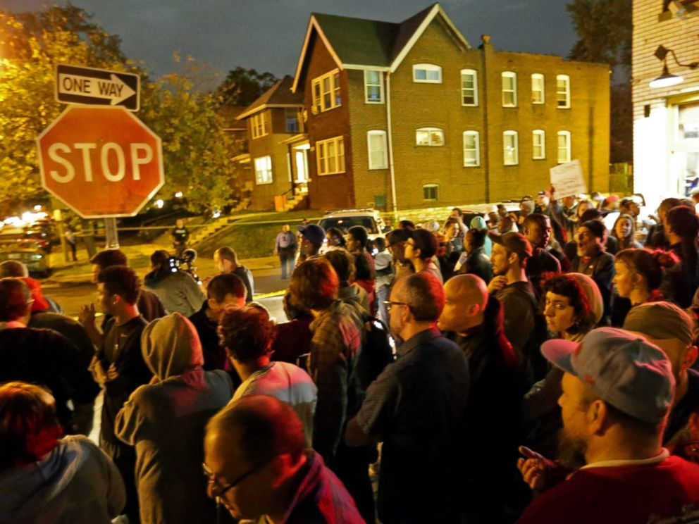 PHOTO: A crowd gathers near the scene in the 4100 block of Shaw Boulevard where a man was fatally shot by an off-duty St. Louis police officer, Oct. 8, 2014.