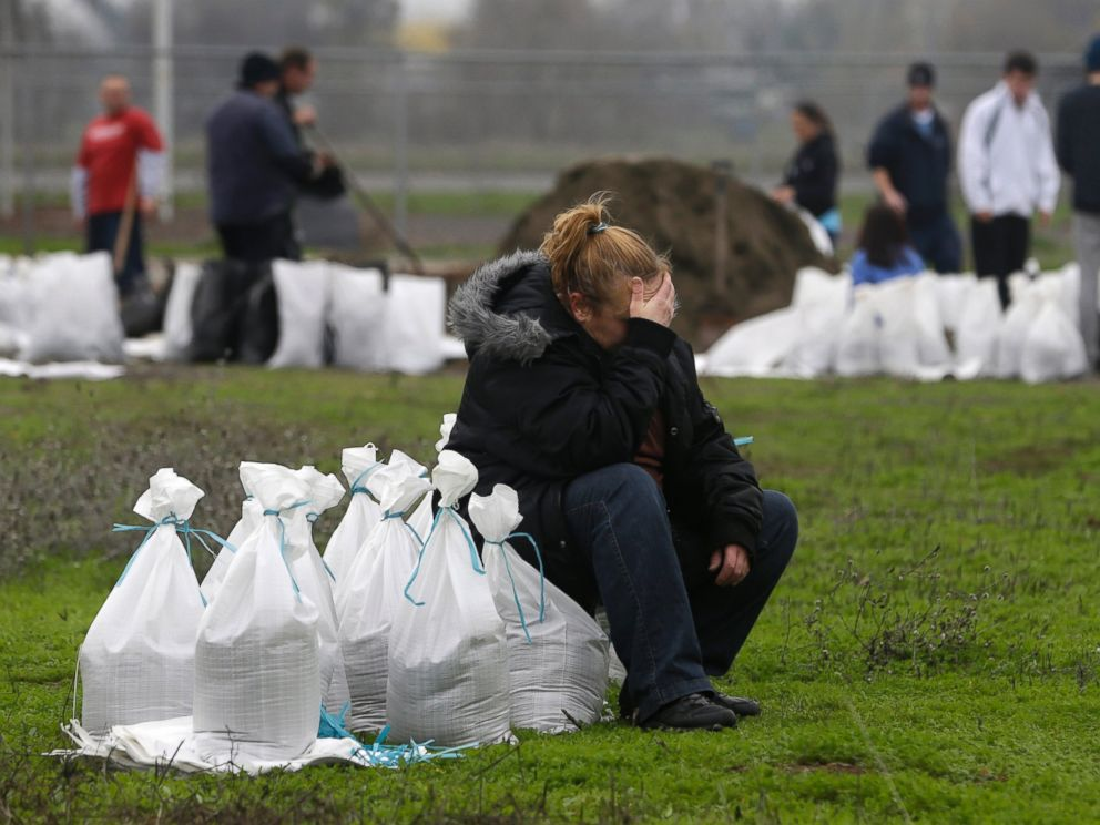 PHOTO: Kathryn Olson rests on a sandbag before carrying it to her vehicle to be used at her home in the Sacramento suburb of North Highlands, Calif., Dec. 10, 2014.