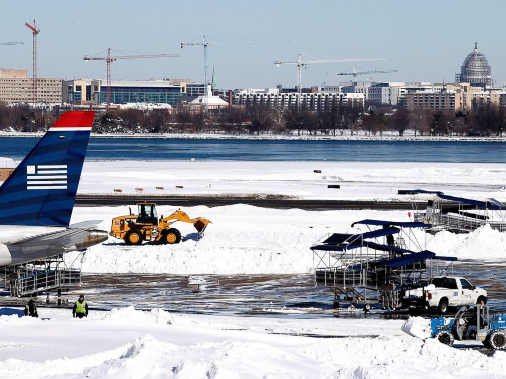 PHOTO:Workers clear snow on the tarmac at Ronald Reagan National Airport, with the U.S. Capitol dome in the background, Jan. 24, 2016 in Arlington, Va.