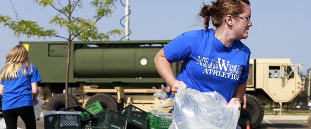 PHOTO: Megan Anllo carries a bag of water to a nearby car, Aug. 3, 2014, in Toledo, Ohio.
