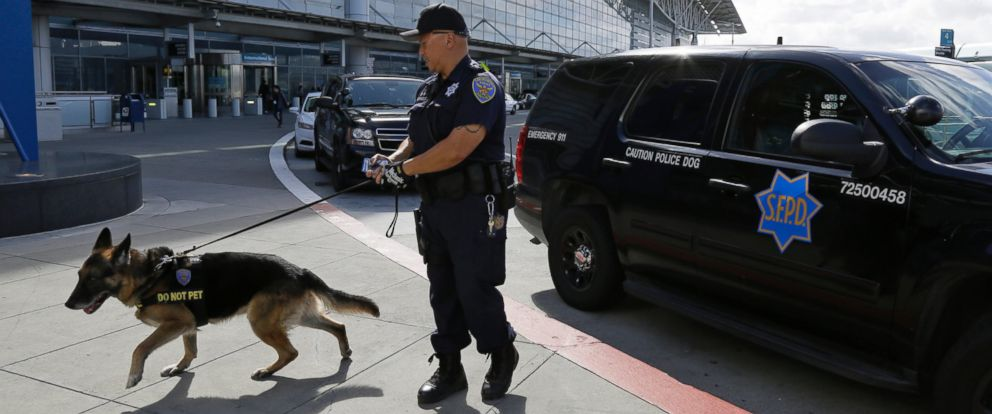 Police officer Dennis Martinez with his German Shepard dog Denny, both with the K9 unit, while on patrol outside the international terminal of San Francisco International Airport, March 22, 2016, in San Francisco.