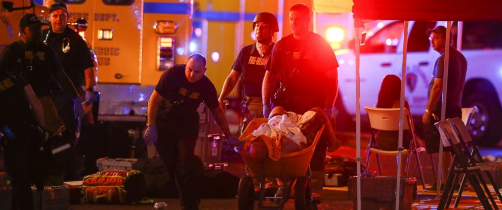 A wounded person is walked in on a wheelbarrow as Las Vegas police respond during an active shooter situation on the Las Vegas Stirp in Las Vegas Sunday, Oct. 1, 2017. Multiple victims were being transported to hospitals after a shooting late Sunday.