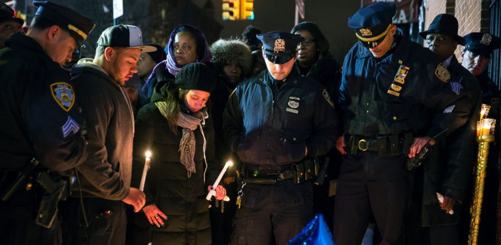 PHOTO: Mourners hold candles, Dec. 21, 2014, during a vigil in New York City near the spot where two police officers were shot and killed.