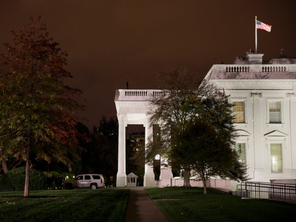 PHOTO: A group of Secret Service police gather on the North Lawn as a member of the Secret Service Counter Assault team surveys from the White House rooftop, Oct. 22, 2014, in Washington.