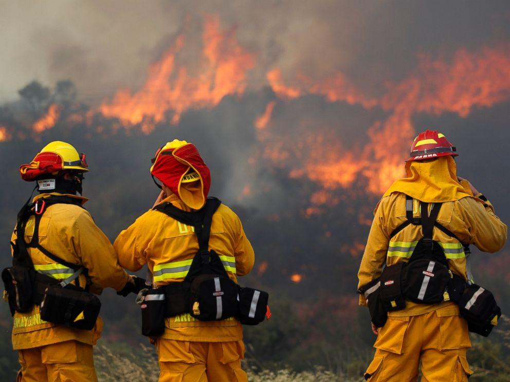 PHOTO: Upland firefighters, from left, Nima Homayounieh, Joseph Armendariz, and Capt. Joe Burna, watch as flames burn toward Highway 94 near Potrero, Calif., June 20, 2016.