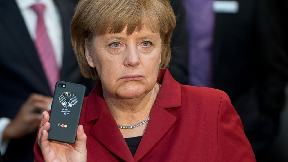 PHOTO: German Chancellor Angela Merkel presents a tap-proof mobile phone of Blackberry during the opening round tour of the worlds largest computer expo CeBIT in Hannover, March 5, 2013.
