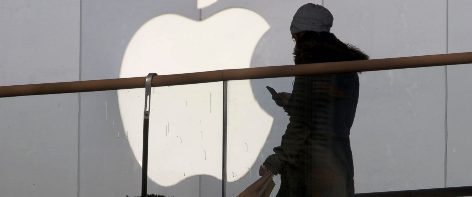 PHOTO: A woman walks past Apples logo.