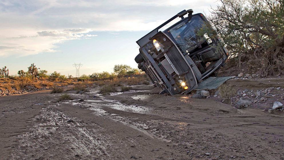 PHOTO: A tour bus lays on its side up against a bank of a wash, July 28, 2013, near Dolan Springs, Ariz.