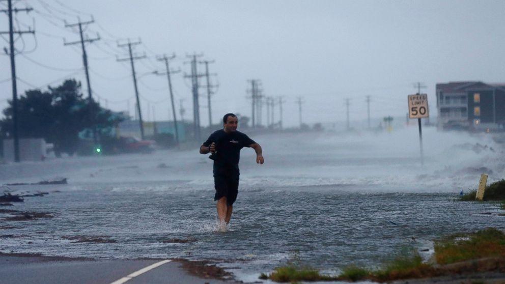PHOTO: A man crosses flooded Highway 64 as Hurricane Arthur passes through Nags Head, N.C., July 4, 2014.