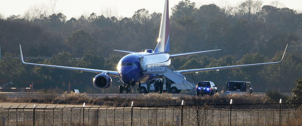 PHOTO: Law enforcement officials stand beneath a Southwest airplane on the tarmac at Hartsfield-Jackson Atlanta International Airport, Saturday, Jan. 24, 2015, in Atlanta.