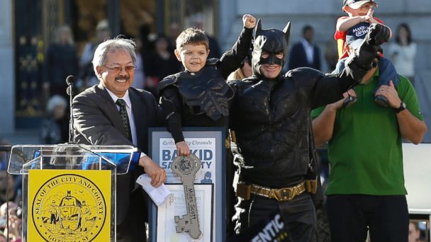 PHOTO: Miles Scott, dressed as Batkid, second from left, raises his arm next to Batman at a rally outside of City Hall with Mayor Ed Lee, left, and his father Nick and brother Clayton, at right, in San Francisco, Nov. 15, 2013.