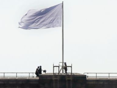 PHOTO: New York City Police officers stand at the base of a white flag flying atop the west tower of the Brooklyn Bridge in New York City on July 22, 2014.