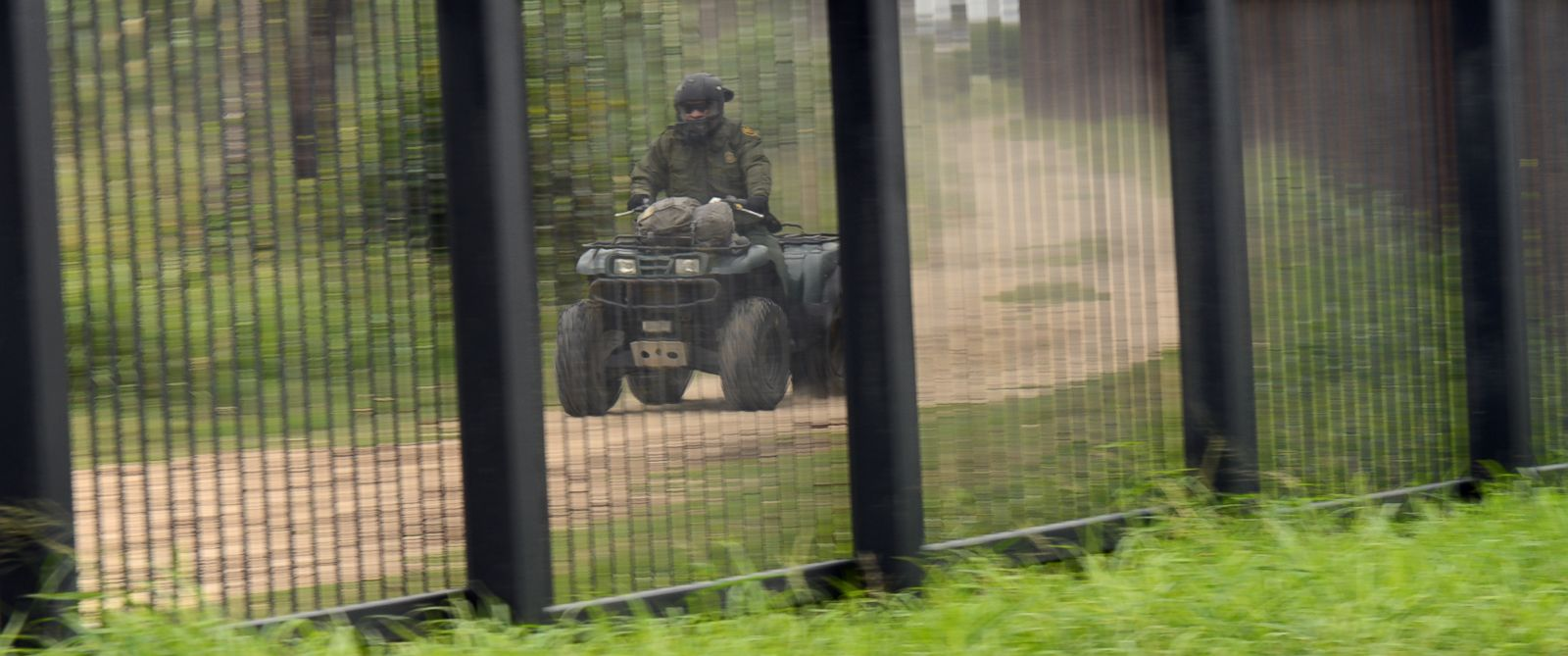 PHOTO: A U.S. Border Patrol agent rides along the Border Fence on an ATV, Nov. 18,2014, near Hope Park in downtown Brownsville, Texas.