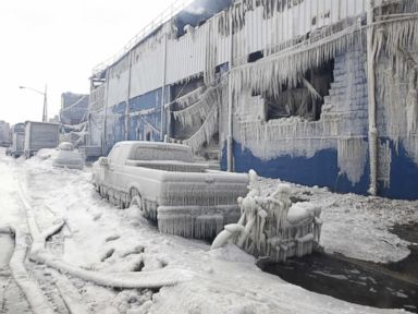 PHOTO: Vehicles and a building are covered with ice as firefighters work to keep a warehouse fire down in the Brooklyn borough of New York, Sunday, Feb. 1, 2015.