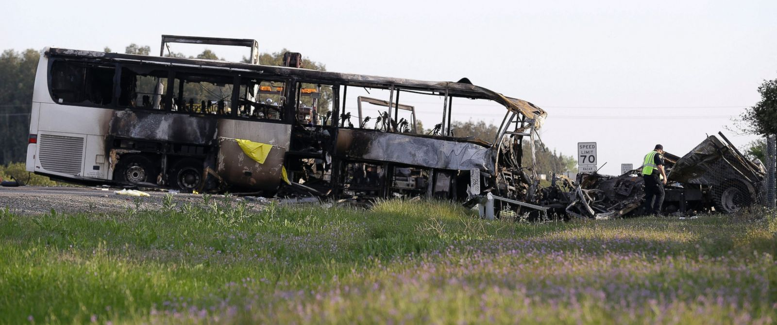 PHOTO: A California Highway Patrol Officer looks over the demolished cab of FedEx truck that crashed into a tour bus, at left, on Interstate 5 Thursday in Orland, Calif., April 11, 2014.