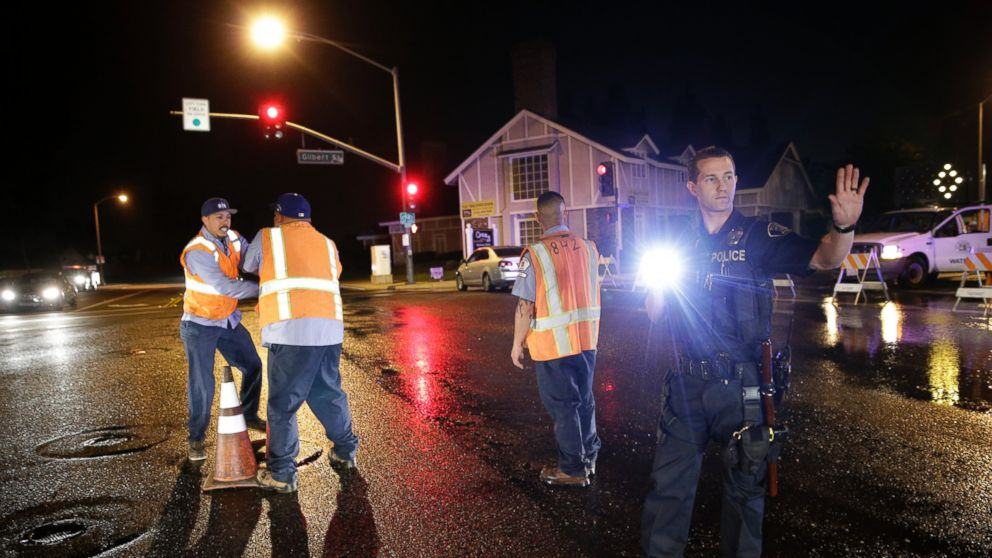 PHOTO: A police officer controls the traffic as workers shut off the water valve on Friday, March 28, 2014, in Fullerton, Calif.