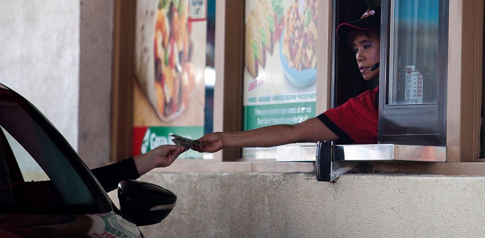 PHOTO: A Carls Jr. employee gives a customer change through a drive-thru window in San Francisco
