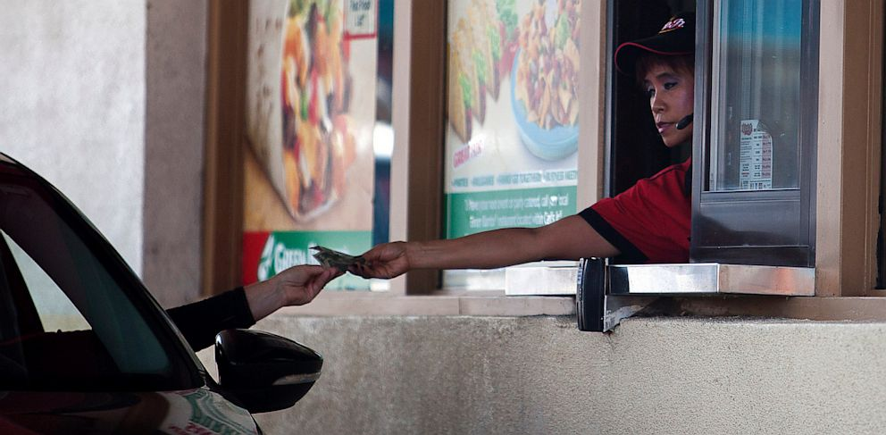 PHOTO: A Carls Jr. employee gives a customer change through a drive-thru window in San Francisco