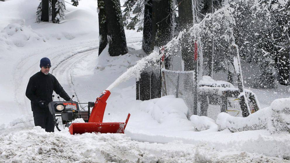 PHOTO: A man clears snow from his driveway after a overnight storm near Echo Summit, Calif.