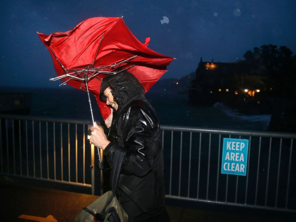 PHOTO: Commuter ML Mann struggles in the wind and rain to make her way to catch a ferry, Dec. 11, 2014, to San Francisco from Sausalito, Calif.