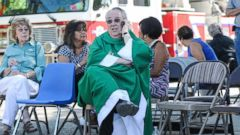 PHOTO: While waiting in a staging area, Holy Cross Catholic Church Pastor John Anderson tries to get in touch with other local churches to warn them of the two explosions that occurred and to be vigilant, Aug. 2, 2015, in Las Cruces, N.M.