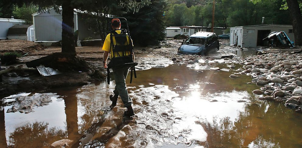 PHOTO: Local resident Ben Rodman walks while helping a friend salvage her home after floods left homes and infrastructure in a shambles, in Lyons, Colo., Friday Sept. 13, 2013.