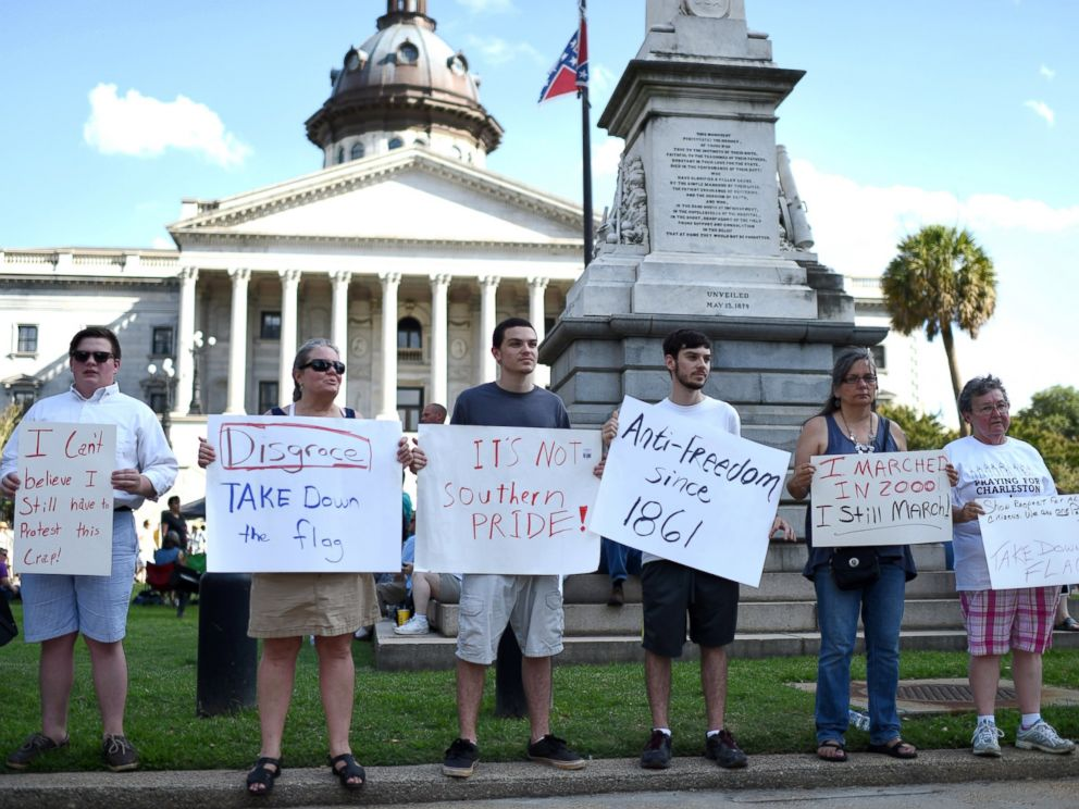 PHOTO: Protesters hold signs in front of the Confederate flag during a rally to take down the flag at the South Carolina Statehouse, June 20, 2015, in Columbia, S.C.