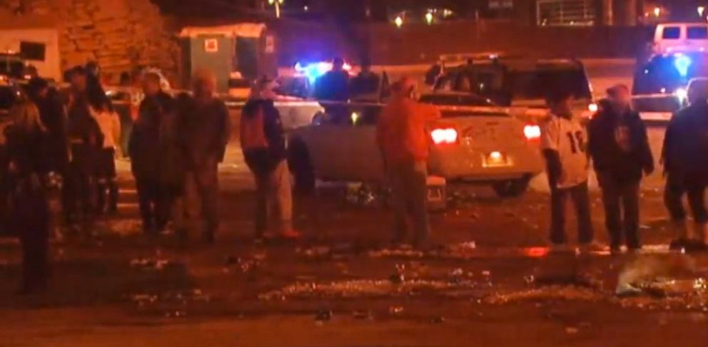 PHOTO: People hang around the area where three people were stabbed, Dec. 12, 2013, in a parking lot at Sports Authority Stadium Field after the Denver Broncos game.